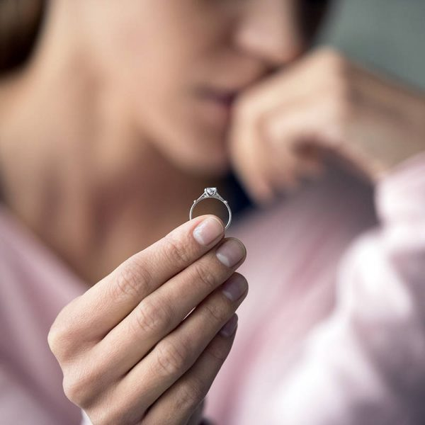 Woman holding ring, deciding whether divorce is right for her or not