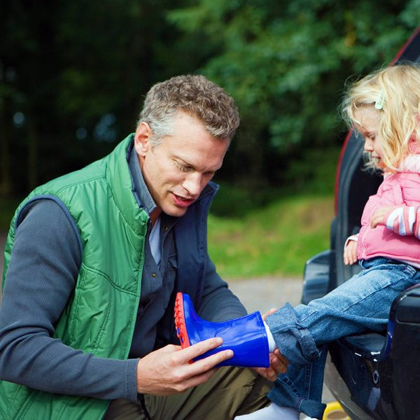 Father Putting Wellington Boot on Child's Foot for Countryside Walk