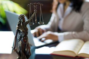 Scales of Justice with Female Attorney in Background