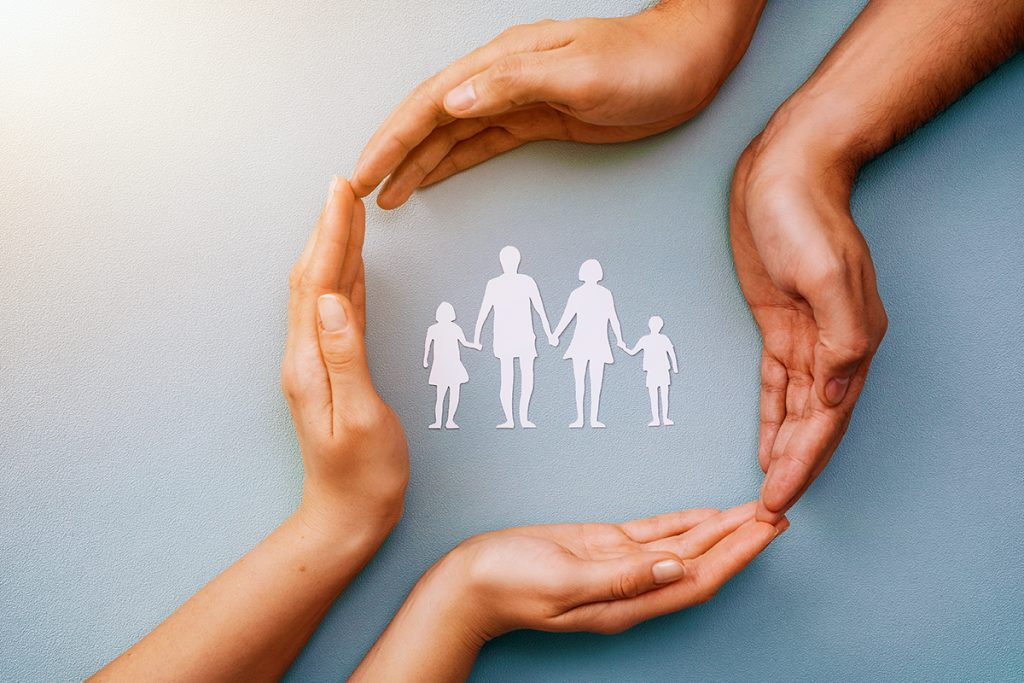 Two pairs of hands protecting family, children.